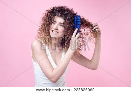 Close-up Beautiful Young Woman Combing Her Curl Hair On Plain Backgrond