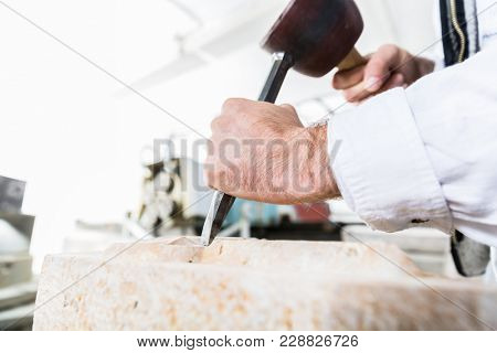 Stonemason cutting boulder with hammer and chisel in workshop