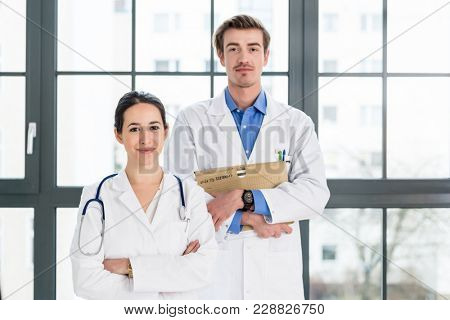 Portrait of two determined physicians wearing white medical gowns while looking at camera with serious facial expression in a modern health center