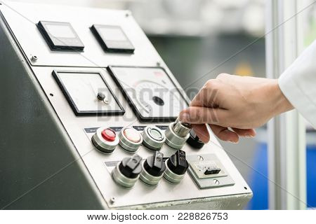 Close-up of the hand of a woman wearing white lab coat, while turning on an industrial machine with mechanical key-operated switch during work in a factory