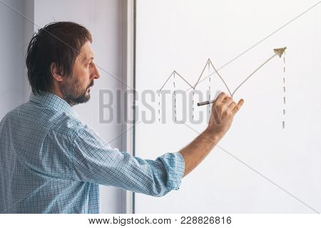 Businessman Drawing Rising Linear Diagram, Conceptual Symbol For Profit Increase And Success In Busi