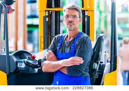 Hardware store employee in warehouse for home improvement equipment with forklift