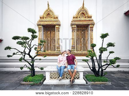 Young Couple In Red Clothes Sitting On The Bench Near Decorative Trees And Golden Windows Of Wat Pho