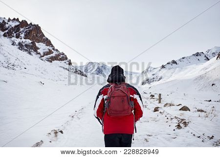 Hiker In Snowy Mountains