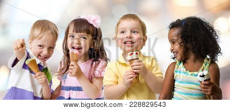 happy kids group eating ice cream at a party in cafe