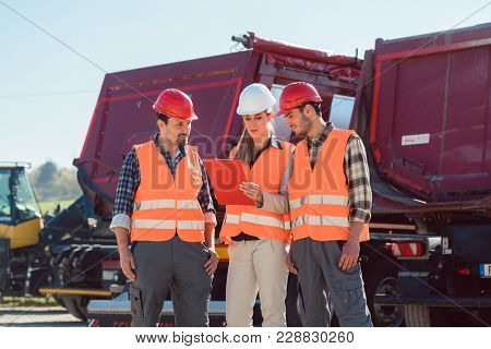 Workers in a heavy transport freight forwarding company looking at vehicles