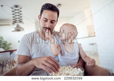 Happy Little Boy Feeding Father With Popcorn