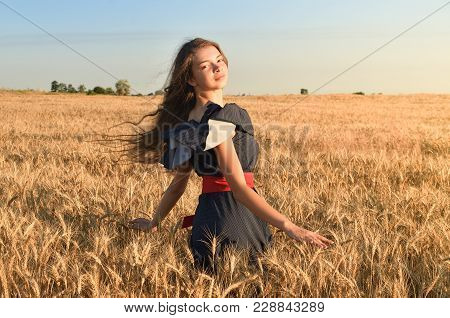 The Girl With The Unraveling Hair Spins In The Field. She Is Surrounded By Wheat Spikes. She Looks I