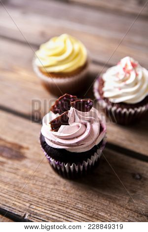 Cupcakes Decorated With Sweet On Wooden Table A