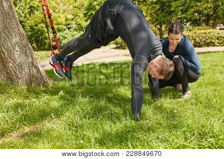 Man sling training with Personal Trainer in summer at the park
