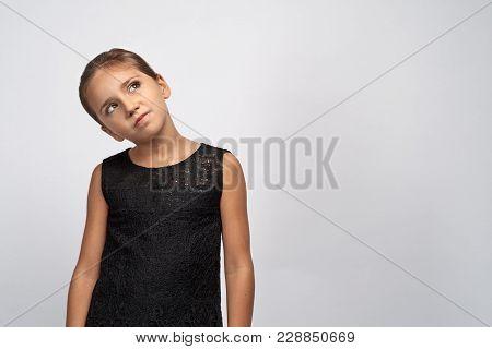 Portrait Of Pensive Pretty Girl Brunette In A Black Dress. Beautiful Doubtful Indecisive Child Looki