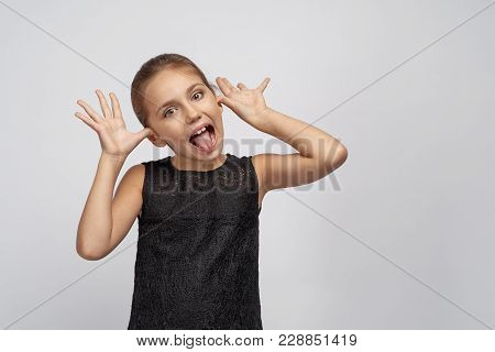 Little Naughty Kid With Black Hair Shows Tongue In Protest, The Girl Misbehaves, Her Tongue In Sign