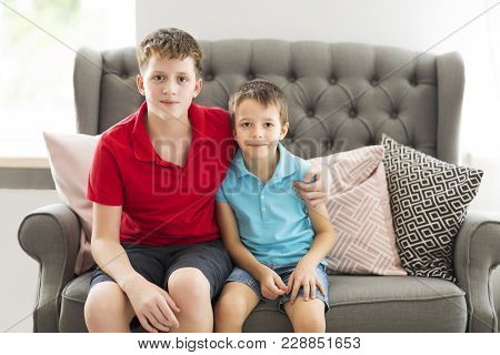 Older brother on the sofa hugging younger brother. Family portrait poster
