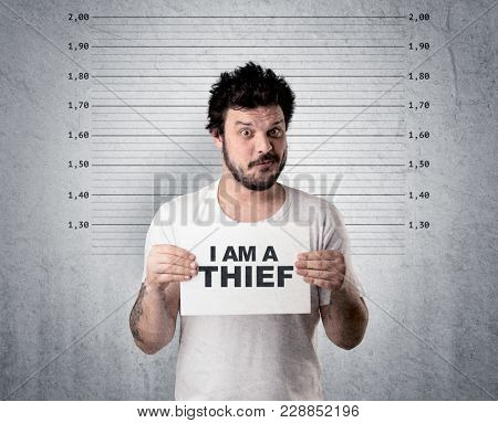 Caugth offender in front of a wall with table in his hand.