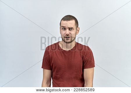 Portrait Of Funny Man With A Discouraged Shocked Surprised Look, Raising One Eyebrow And Opening His