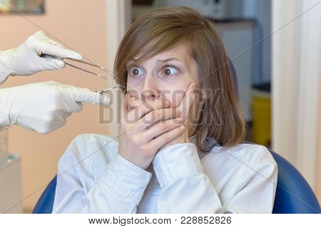 A Young Woman Is Shocked By The Fear And Horror Of Dental Instruments That She Looks At With Her Eye