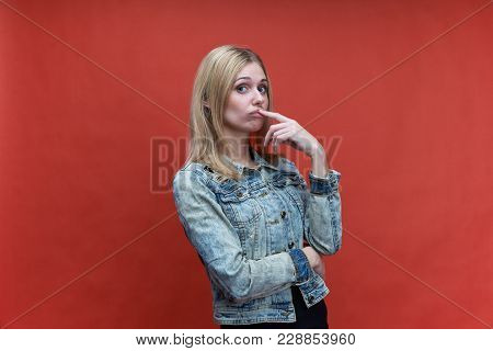 Studio Portrait On Red Background Girls Teenager With Long Hair And A Gaze Directed At The Camera. T