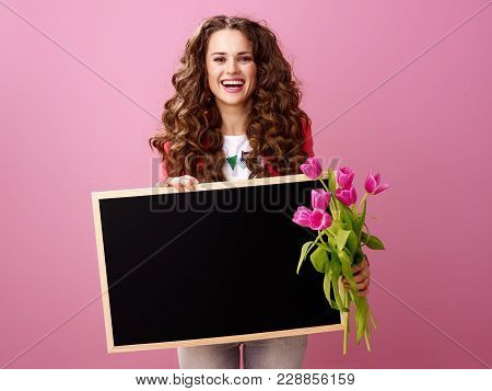 Happy Young Woman With Bouquet Of Tulips Showing Blank Board