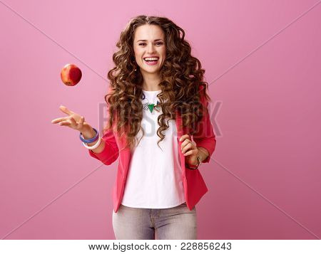 Smiling Trendy Woman On Pink Background Throwing Up An Apple
