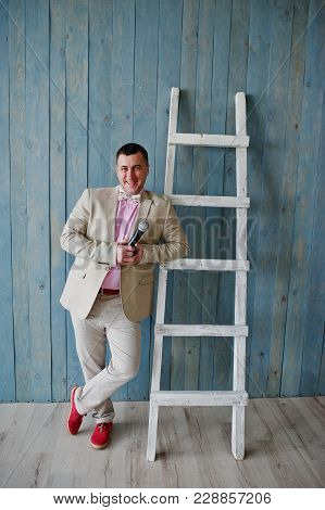 Handsome Man In Beige Suit And Pink Shirt With Microphone Against Ladder Background On Studio.  Laug