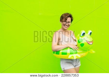 Beautiful Woman With A Green Inflatable Circle Frog On The Background Of A Green Wall. The Concept O