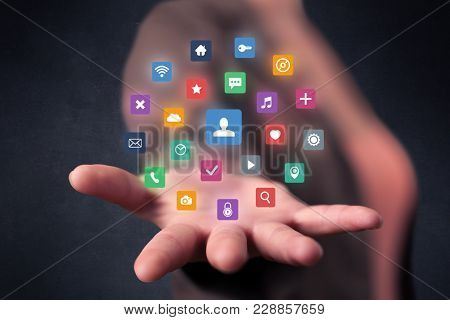 Colorful multimedia icons in the hands of a young casual businesswoman