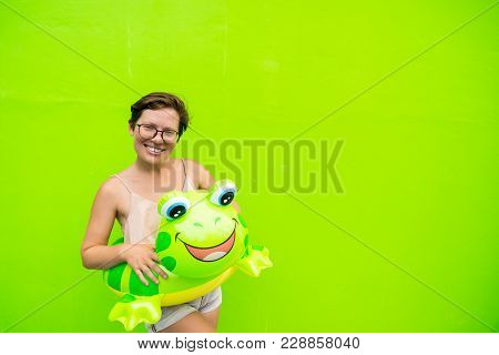 Beautiful Young Woman With An Inflatable Circle Frog On A Green Wall Background With Glasses Smiling