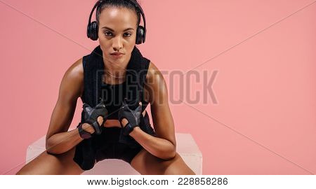 Sporty Woman With Towel Around Her Neck Enjoying Music