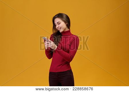 Portrait Of Happy Smiling Girl Isolated On Orange Background, Is Half-turned To The Camera And Holdi