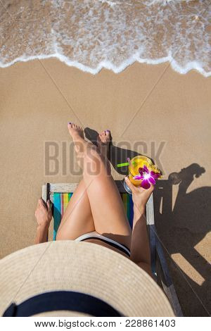 Woman At Beautiful Beach Sitting On Chaise-lounge And Drinking Cocktail Top View