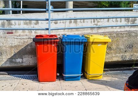Three Colorful Trash Containers For Garbage Separation In Sunny Street