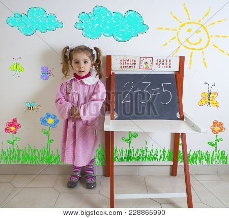 Tender Child In Smock Next To The Chalkboard