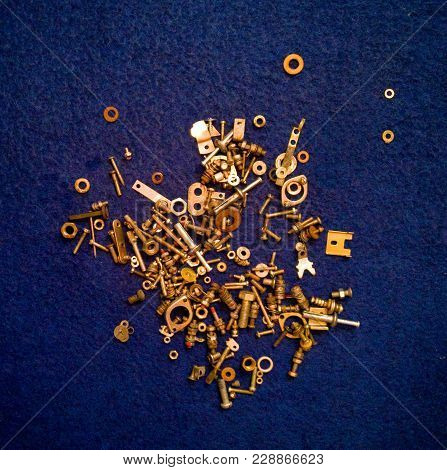 On A Blue Background With An Original Illumination There Is A Heap Of Small Spare Parts From Various