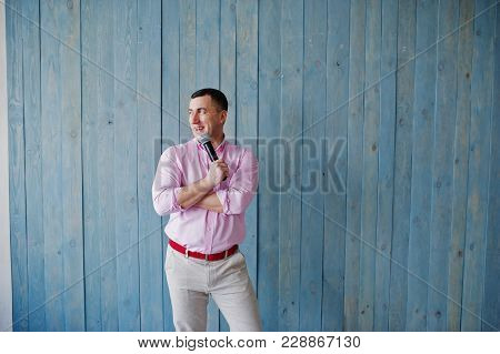 Handsome Man In Pink Shirt With Microphone Against Blue Wooden Wall Background On Studio. Toastmaste