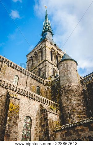 Low View Of Stone Abbey With Statue Of Archangel Michael On Spire Against Blue Sky On Le Mont Saint-
