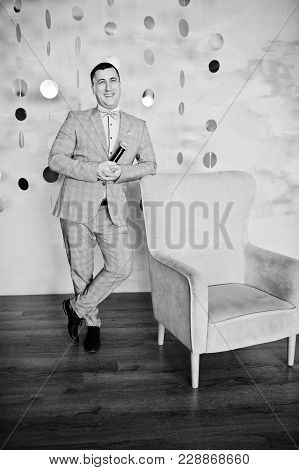 Handsome Man In Gray Suit With Microphone Against Chair Background On Studio.  Laughs Face Of Toastm