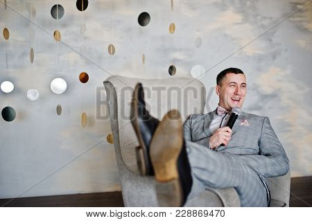 Handsome Man In Gray Suit With Microphone Sitting On Chair Background Studio.  Laughs Face Of Toastm