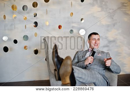 Handsome Man In Gray Suit With Microphone Sitting On Chair Background Studio. Toastmaster And Showma