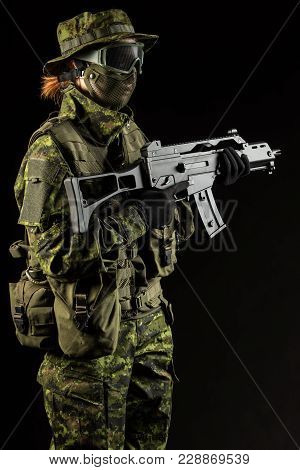 Portrait of armed woman with camouflage. Young female soldier observe with firearm. Child soldier wi