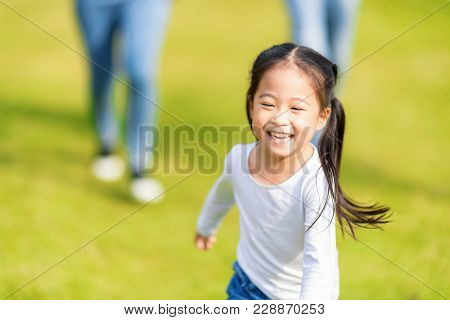 Little Girl Is Running With Parents In The Park. Young Family With Little Kid Having Fun In Nature.