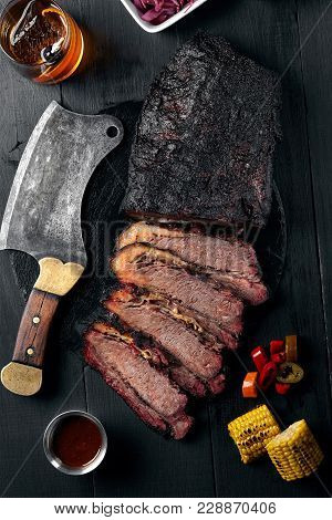 Fresh Brisket Bbq Beef Sliced For Serving Against A Dark Background With Sauce, Hot Peppers And Corn