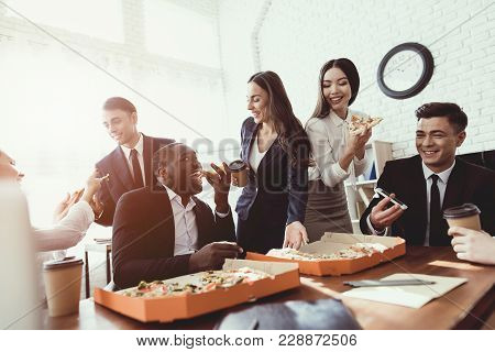The Office Staff Eat Pizza And Drink Coffee In The Business Office. They Have A Break In Their Work.