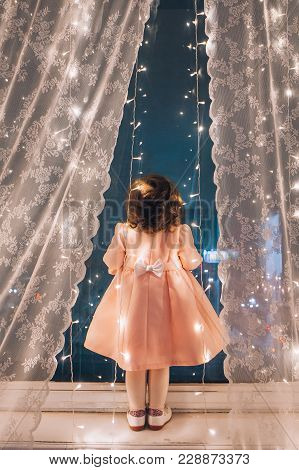 Cute Child Girl Stay Near The Window And Looking At The Stars. Little Kid Stay At Windowsill Around