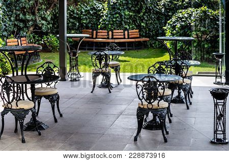 Terrace With Vintage Tables And Chairs In A Cafe Or Restaurant Under A Canopy In A Beautiful Garden