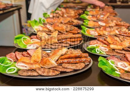 Mix Of Various Types Of Barbecue Meat Decorated With Salad And Onion On Buffet Table. Female Waiter