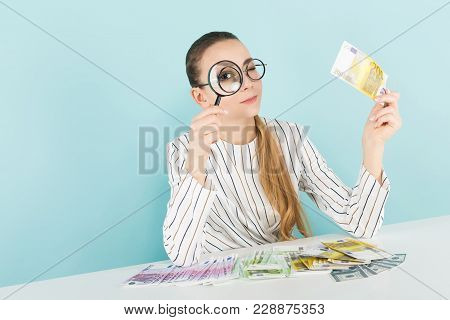 Portrait Of Attractive Woman In Striped Shirt And Eyeglasses Isolated On Blue Background Looking Thr