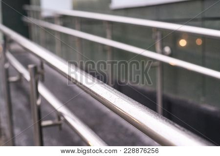 Blurred Background. Metal Smooth Handrails. Building Wall.