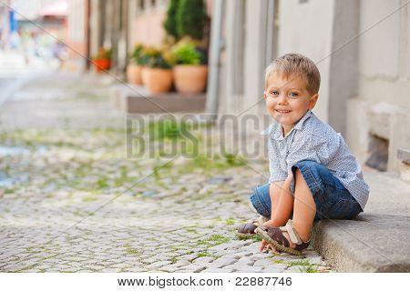 little boy sits on the doorstep on a city street