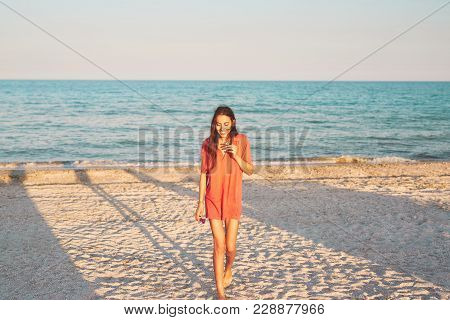 Beautiful Young Woman In Mans Red Polo Walking Along The Beach Against The Sea And Sky. Happy Woman