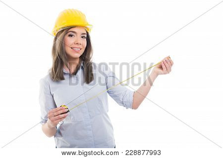 Attractive Female Constructor Holding Tape Line Wearing Hardhat.